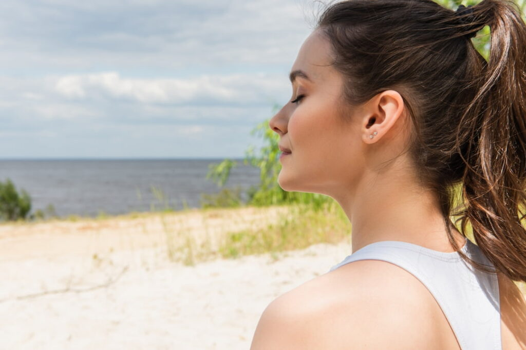 a girl with close eyes relaxing by the sea