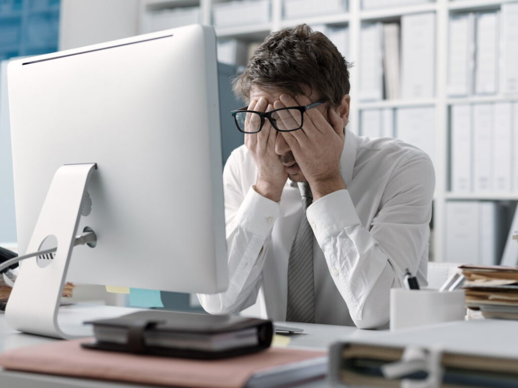a man at his working desk rubbing his eyes