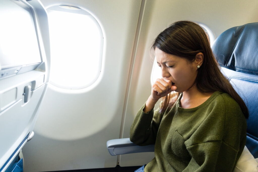 a woman feeling sick inside the airplane