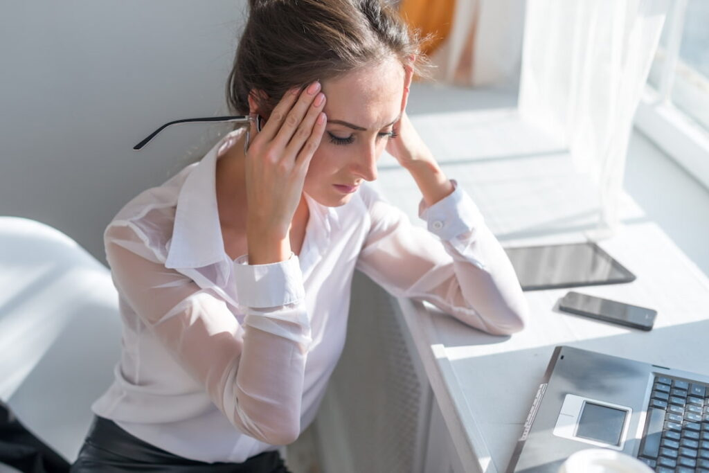a woman with headache trying to overcome the pain
