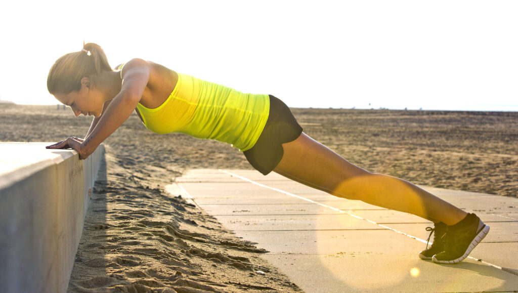 Woman doing Press ups on a beach
