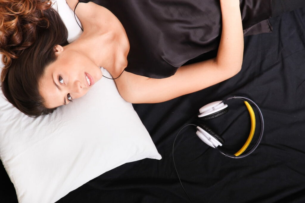 a woman lying on the bed by the headset