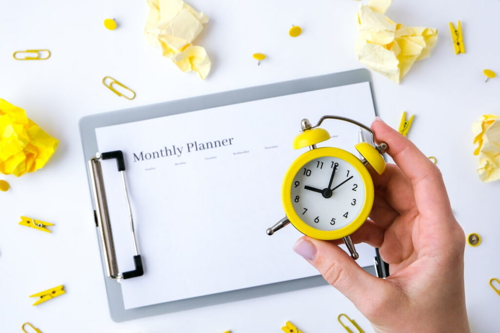 Monthly goals planner and yellow alarm clock