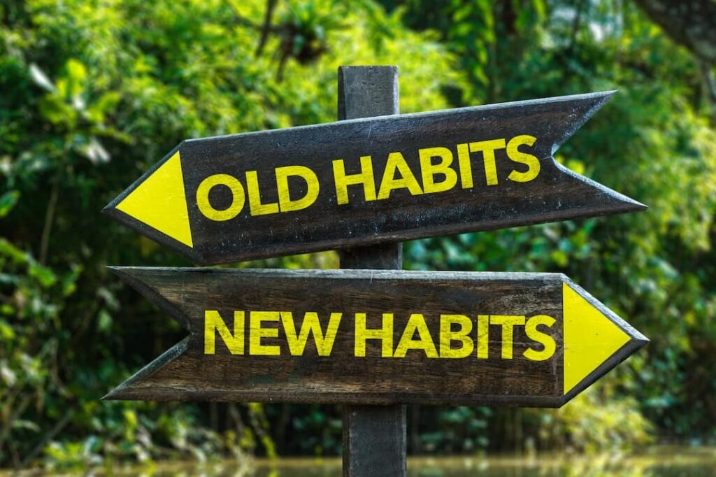 Old Habits - New Habits signpost showing the way in the woods