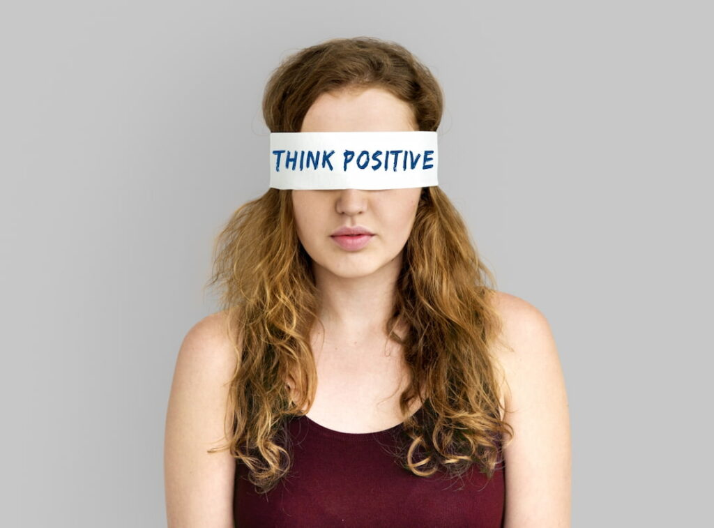 a woman with covered eyes with Think Positive note