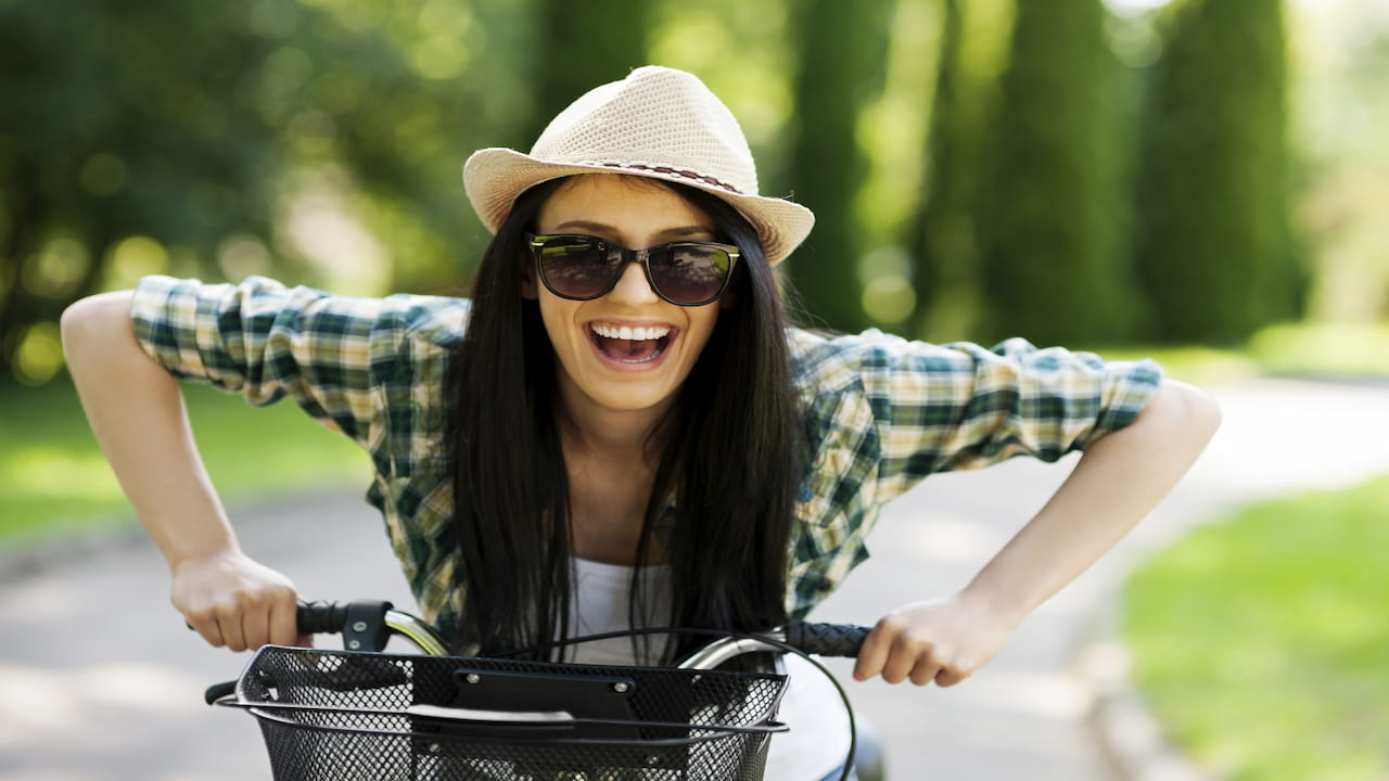 happy woman with hat and sunglasses riding the bicycle