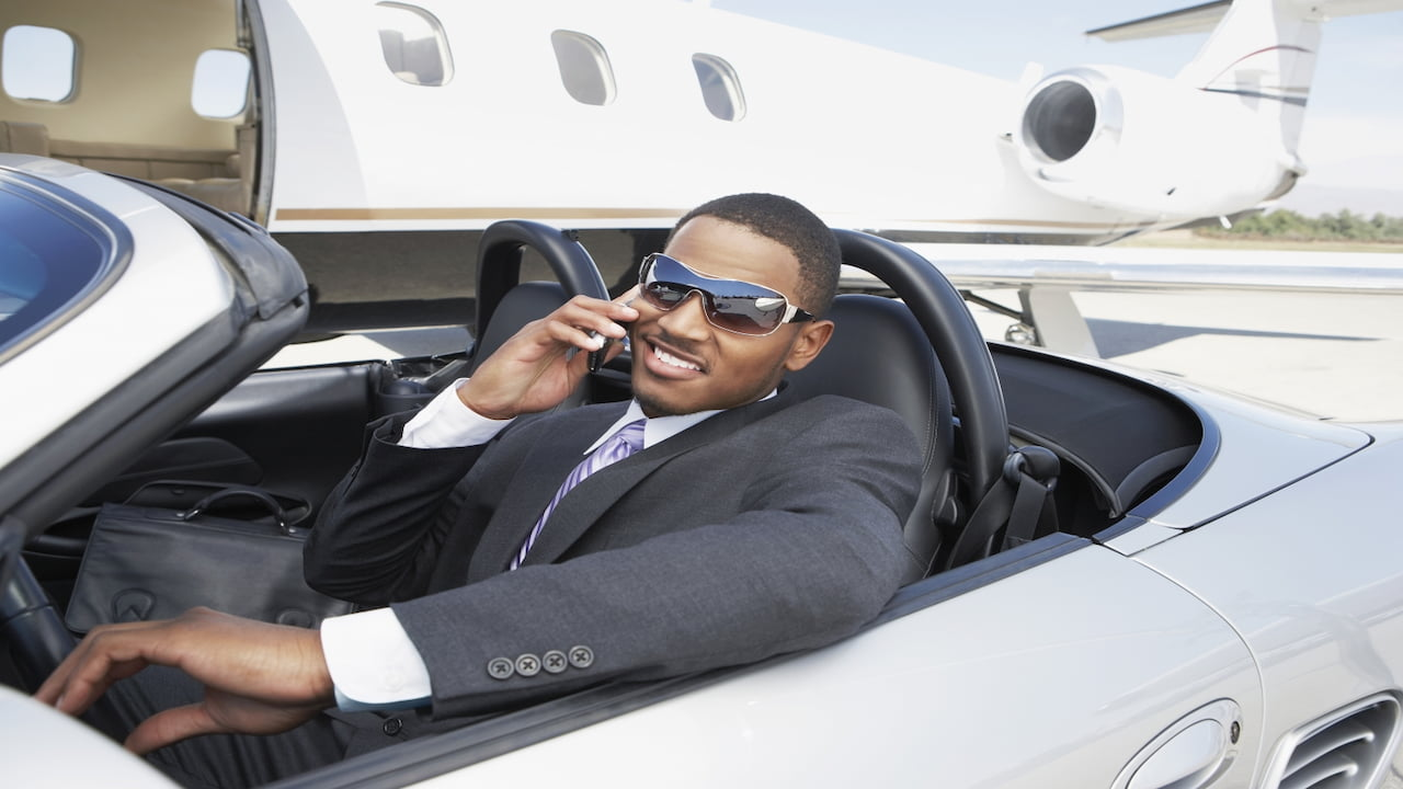 a businessman in convertible smiling and holding cellphone