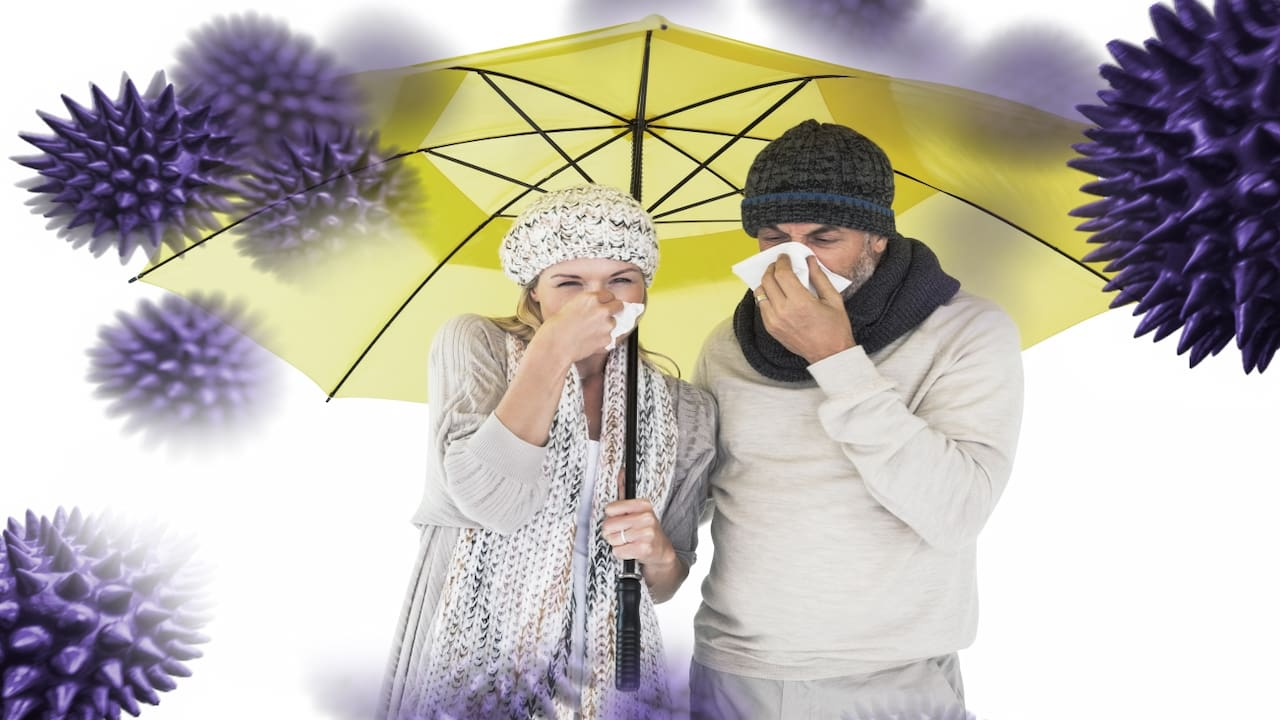 Couple sneezing in tissue while standing under the yellow umbrella