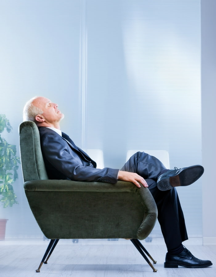 a man sitting in an armchair with his eye closed
