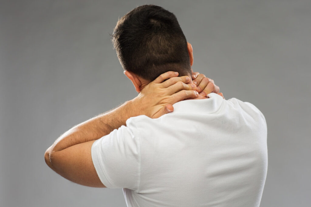 a man in pain touching his neck