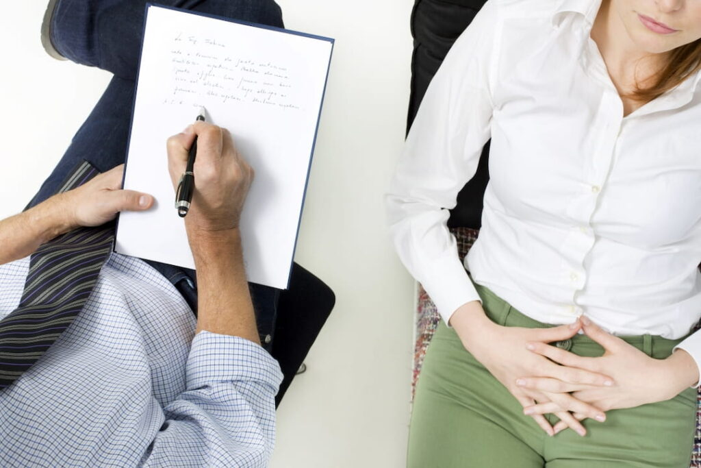 the therapist taking notes during the session with his patient