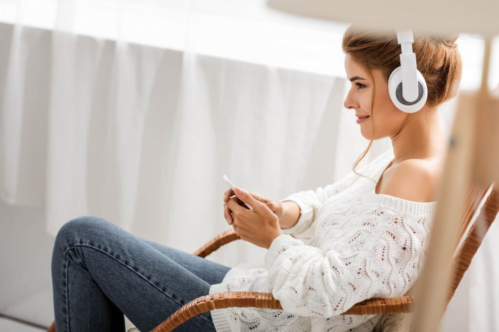 a woman sitting in the chair with headphones on her head