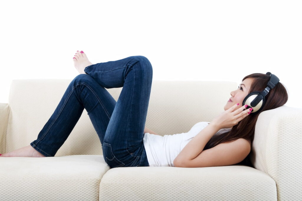 a woman lying on the sofa and listening to audios on her headphones