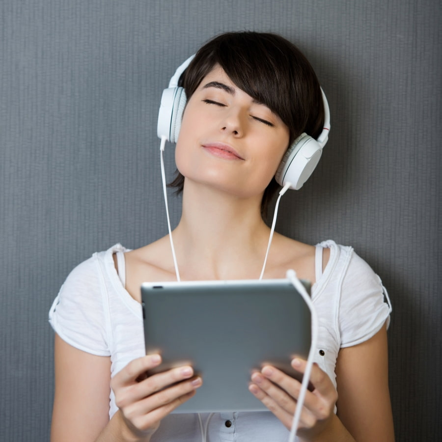 a woman listening to audios on her notebook