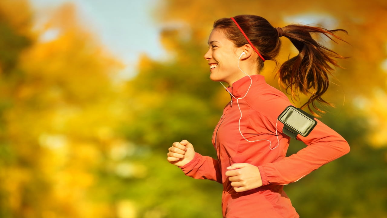 a young woman with earphones in her ears running