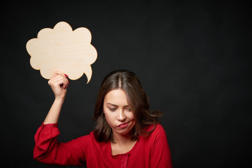 a woman holding a thinking bubble above her head