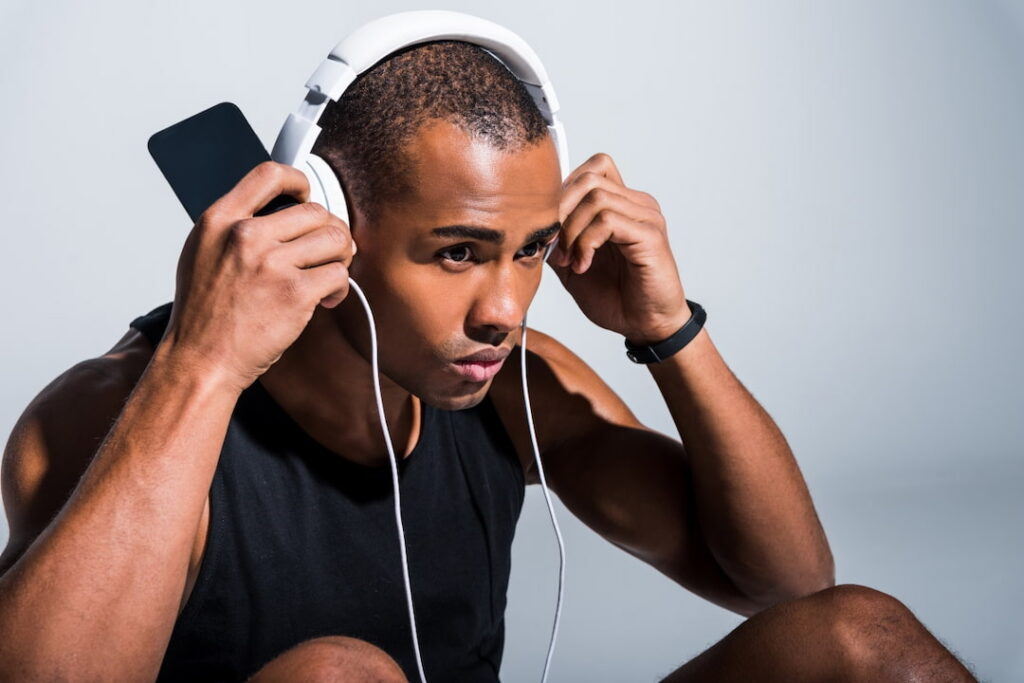 young athlete using headphones and cellphone