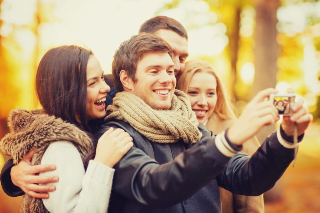 a group of friends with photo camera in autumn park
