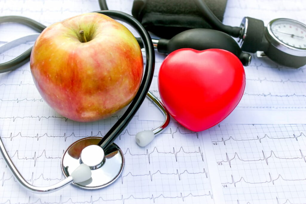 an apple, a red heart and a stethoscope