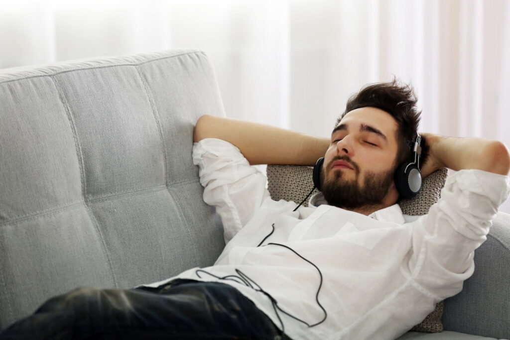 zoung man listening to the audios with headphones on his ears
