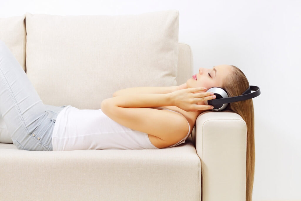 a girl lying on the couch with headphones on her head