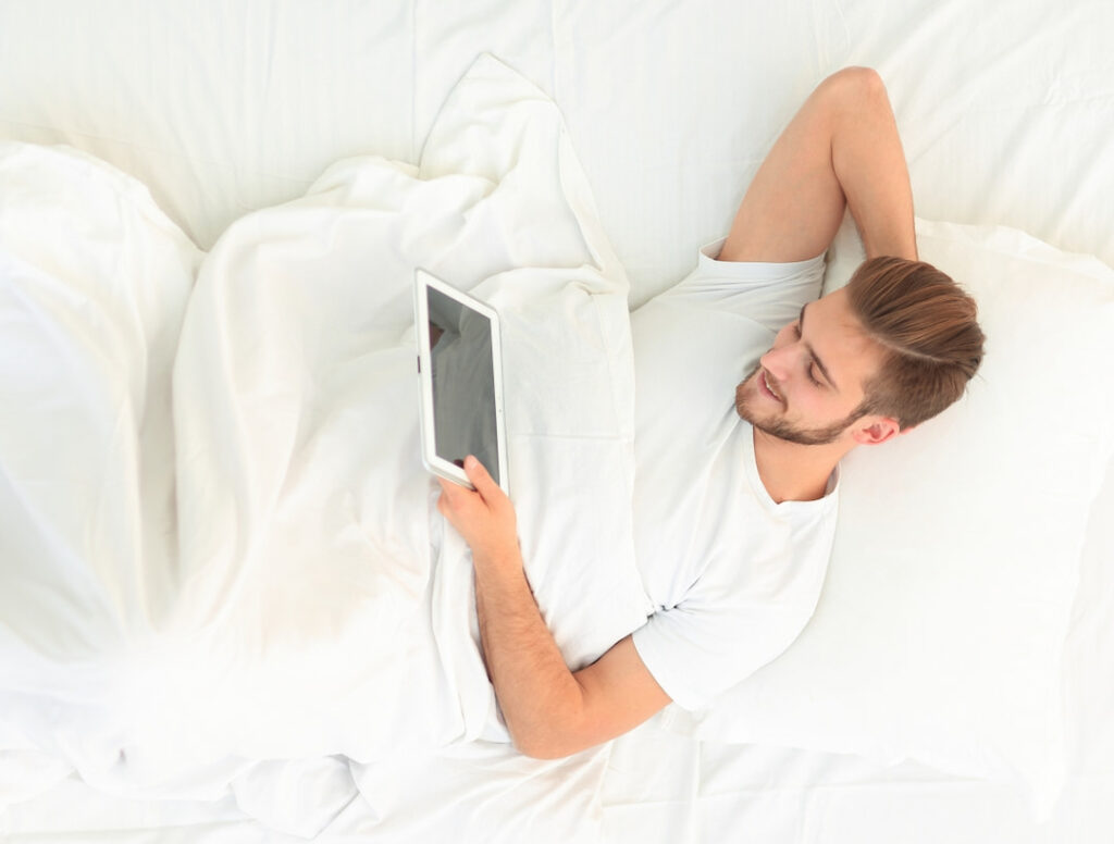 man in bed holding tablet