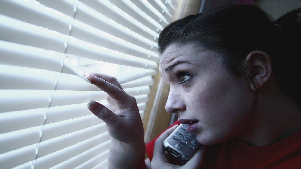 a girl on the phone, peeking out a window