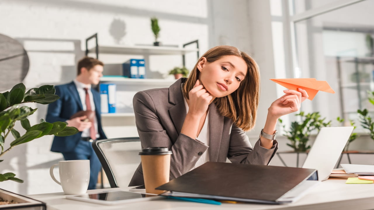 a woman sitting at the desk in the office and holding paper airplane in her hand