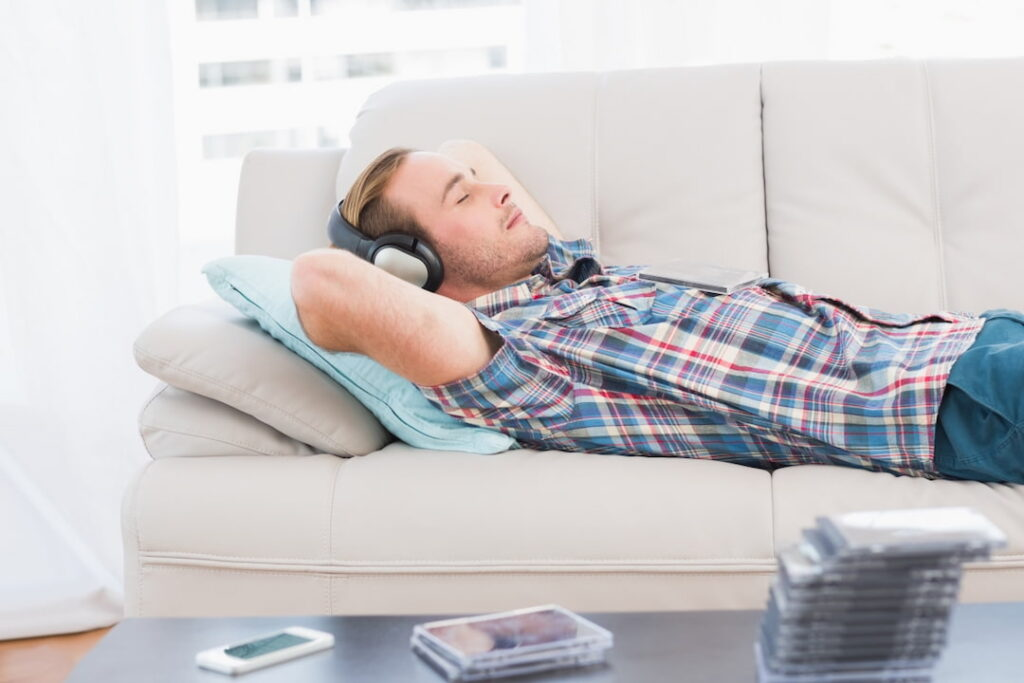 a man lying down on the couch and listening to hypnosis audios