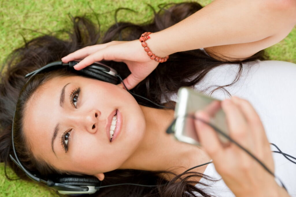 a woman lying down on the grass and listening to audios
