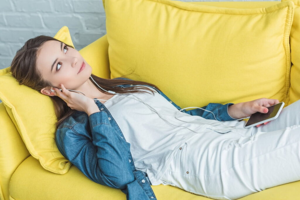 young woman lying on the couch and listening to audios