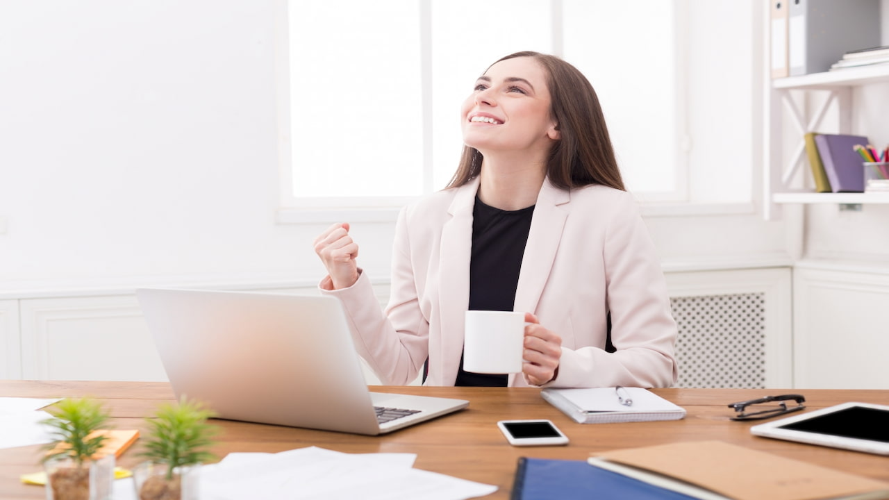 a woman in her office feeling happy about her success