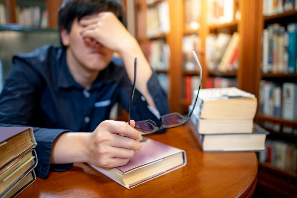 a tired student sitting in the library