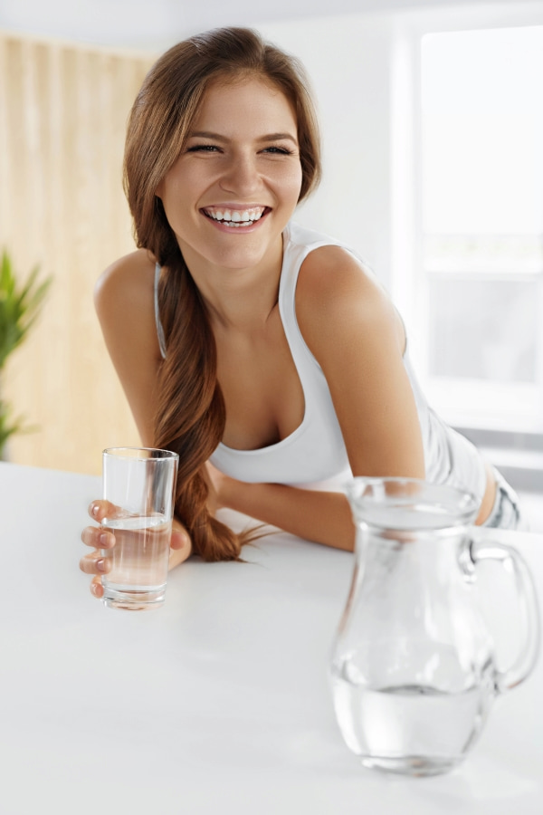 a smiling girl holding a glass of water