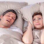 a man snoring beside his wife