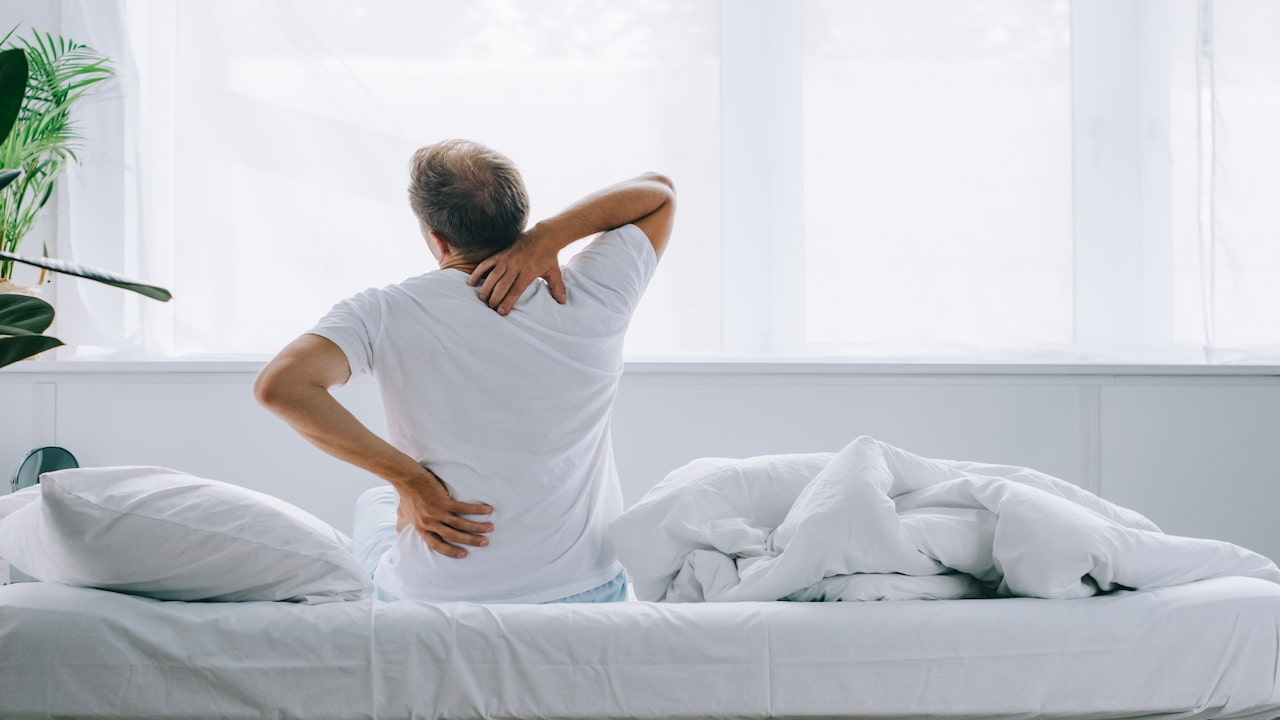 Back view of man sitting on bed and suffering from the back pain