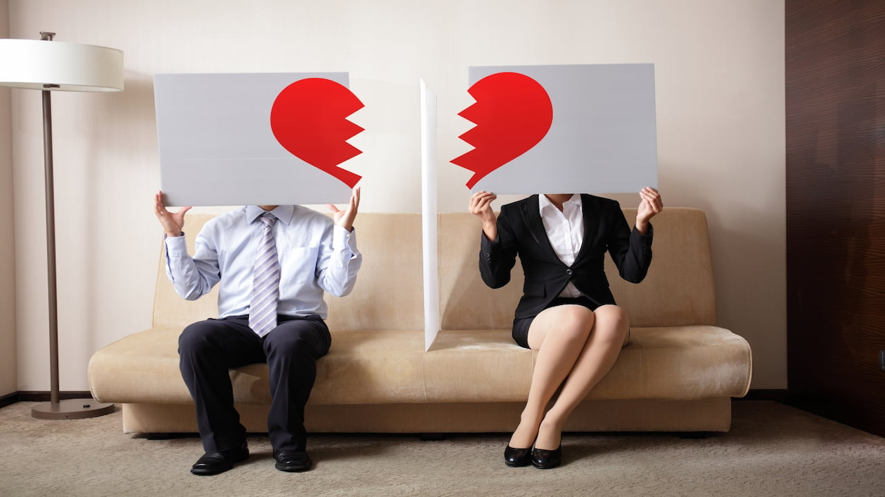 a separated couple sitting on the couch and holding illustrations of a broken heart