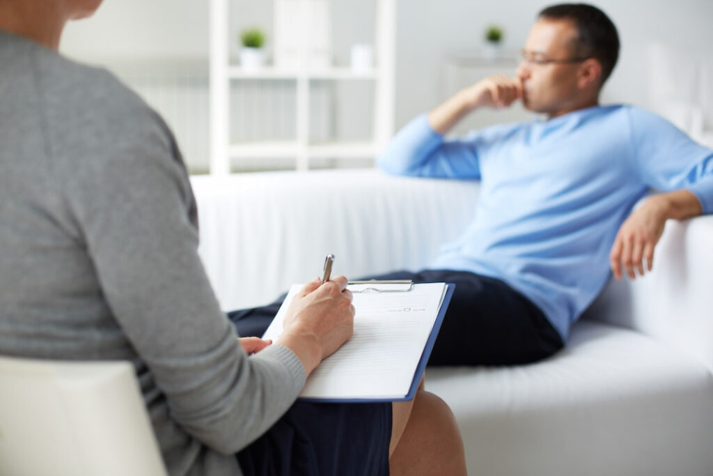 a man sitting on the couch at his hypnosis therapy session
