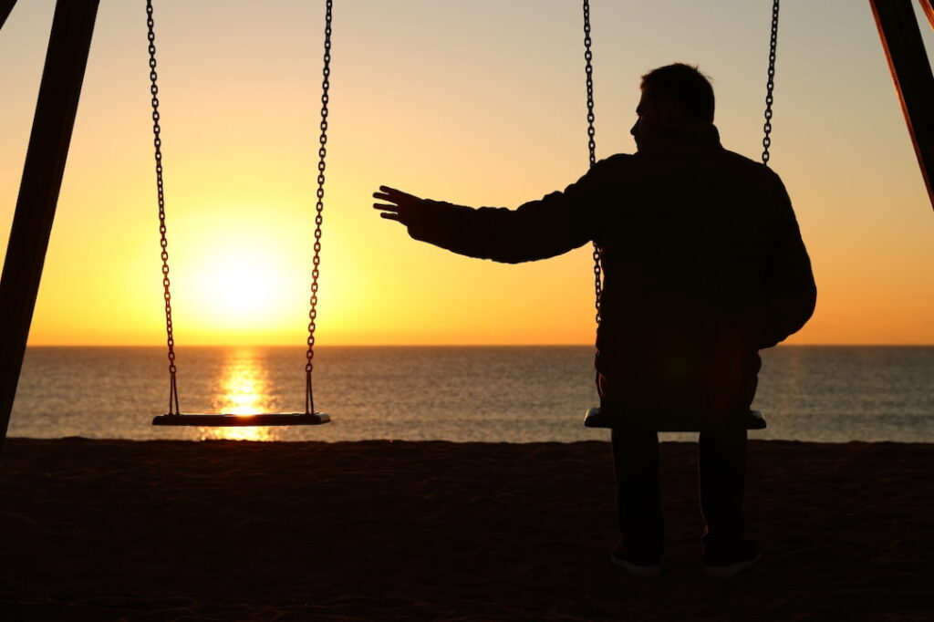 lonely man sitting on the swing by the sea