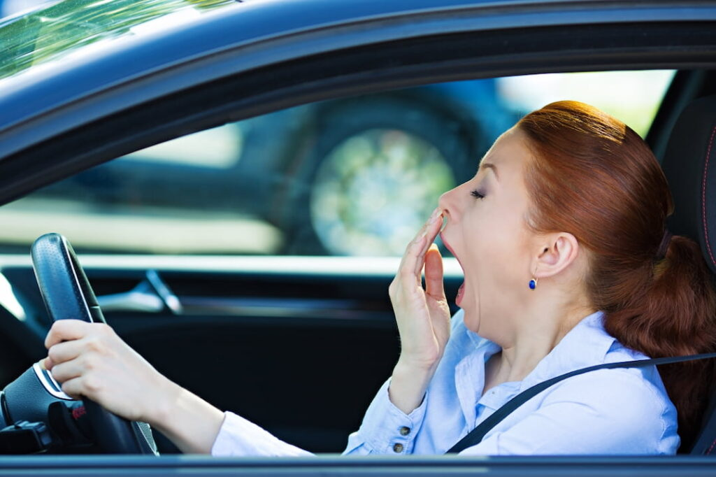 fatigued woman driving a car