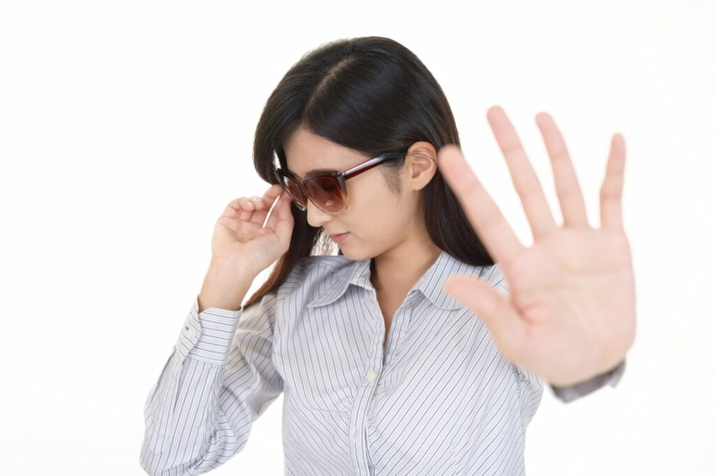a woman with sunglasses showing stop hand gesture